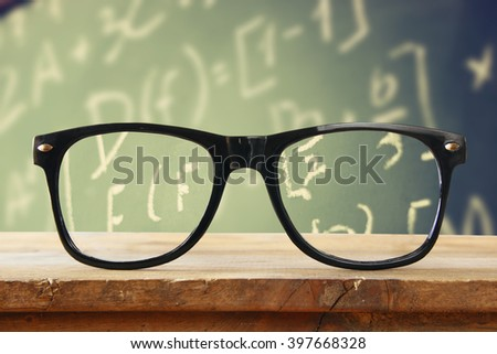 hipster glasses on a wooden rustic table in front blackboard with math formulas and calculation. vintage filtered
