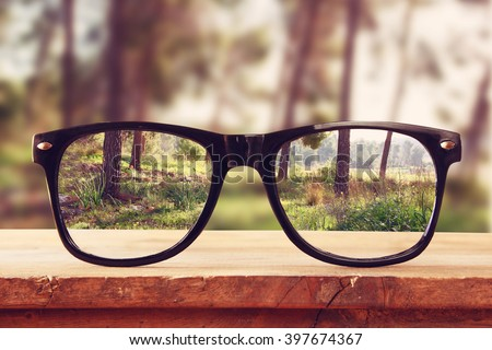hipster glasses on a wooden rustic table in front of the forest. vintage filtered