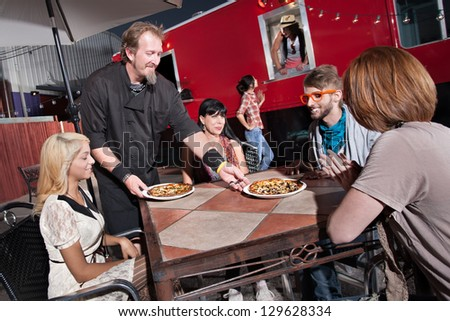 Hipster group served pizza by mobile cafe chef - stock photo