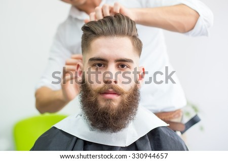 Hipster guy getting ready for the shooting at the barber.