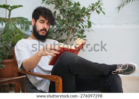 hipster guy reading a red book outdoors and relaxing - stock photo