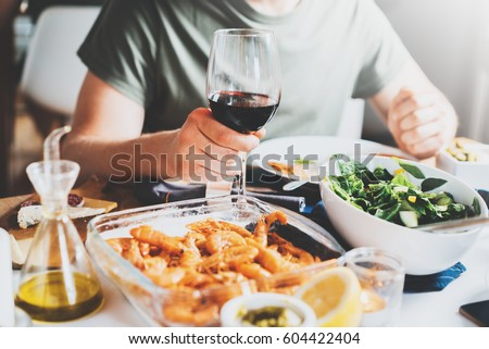 Hipster guy toasting with glasses of red wine while celebrating anniversary at cozy atmosphere, holidays and enjoyment concept