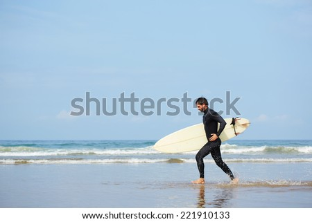 Hipster guy with white surfboard running along the beach touching waves, beautiful surfer man running at the beach with his surfboard, surfer man runs out the ocean carrying surfing board