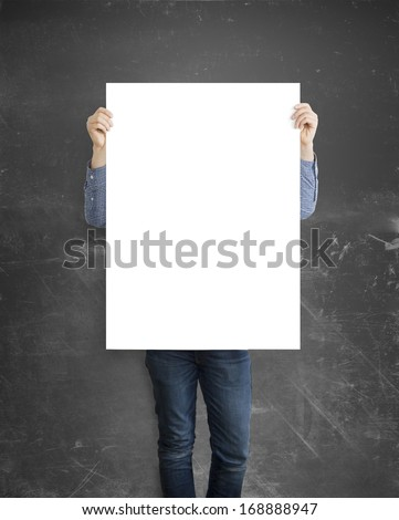 hipster holding blank paper on green wall