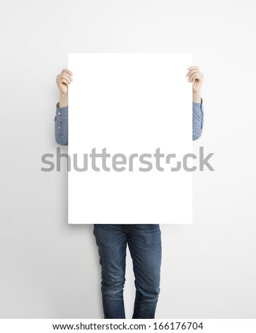 hipster holding poster on concrete wall - stock photo