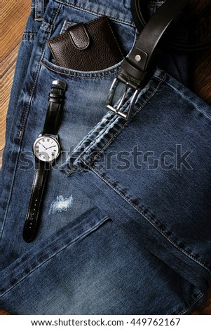 hipster jeans with watches and wallets on a wooden background