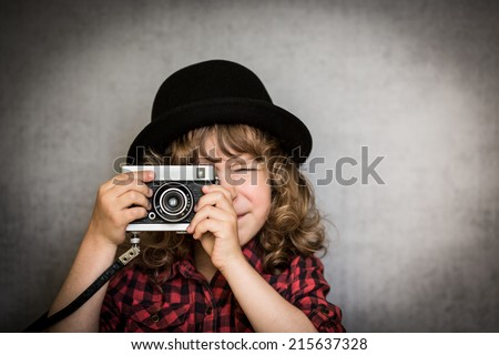 Hipster kid taking a photo using vintage film camera - stock photo