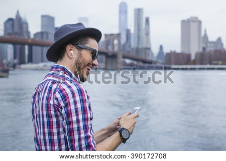 Hipster listening music with his smartphone in Brooklyn, New York - stock photo