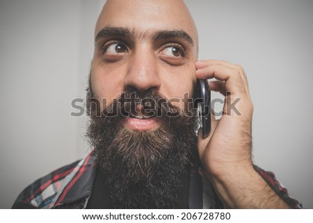 hipster long bearded and mustache man with shirt squares calling with cellphone