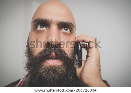 hipster long bearded and mustache man with shirt squares calling with cellphone - stock photo