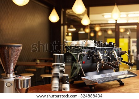 Hipster looking coffee shop ready to open for the day with a clean and tidy counter and well-maintained shiny coffee machine on the the wooden surface - stock photo