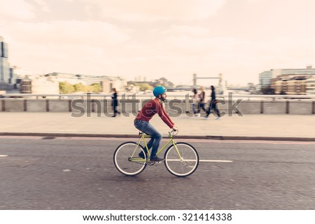Hipster man cycling on London bridge with Thames river and Tower Bridge on background. He is riding a fixed gear bike and wearing blue jeans and a red sweater. Panning technique.