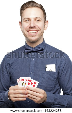Hipster man in bow tie looking stylish playing poker holding royal flush