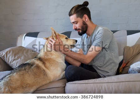 hipster man petting and rubbing his dog, loving affection relationship bond between owner and pet - stock photo