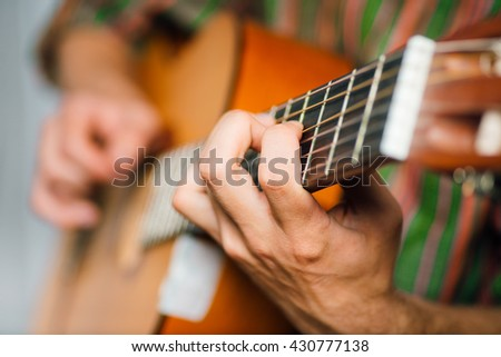 hipster man playing classical guitar, wears a hat and glasses, isolated on a gray background - stock photo