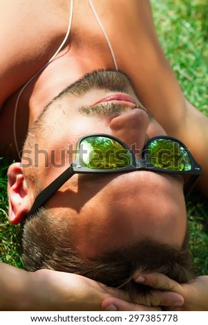 Hipster man relaxed and lying on the grass in city park,in sun reflecting sunglasses,mans fashion style. Close up portrait of Stylish young beard man,sportsman with sexy fit body rest. Summer concept - stock photo