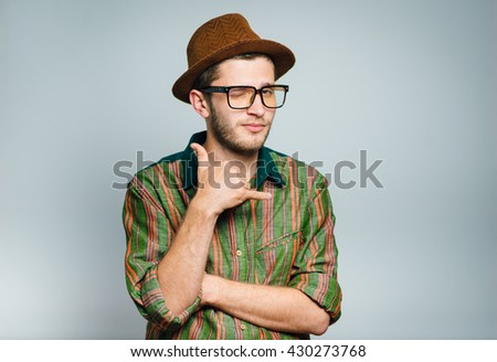 hipster man shows gesture call me, wears glasses and hat, isolated on gray background - stock photo