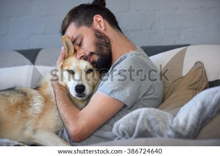 hipster man snuggling and hugging his dog, close friendship loving bond between owner and pet husky - stock photo
