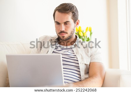 Hipster man using laptop on couch at home in the living room