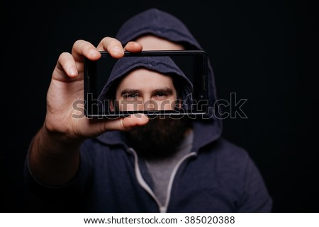 Hipster man with a beard taking picture smartphone self-portrait, screen view, snapshot studio on a black background