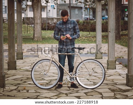 Hipster man with a fixie bike and smartphone in a park outdoors - stock photo