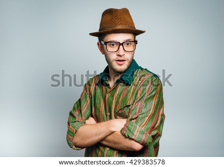 hipster man with a hat is offended, isolated on a gray background - stock photo