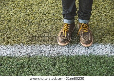 Hipster man with fashion brown leather boots on Football field