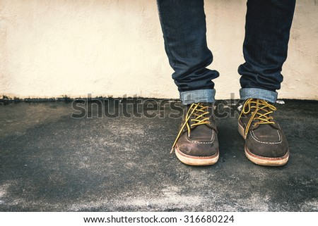 Hipster man with fashion brown leather boots on the ground - stock photo