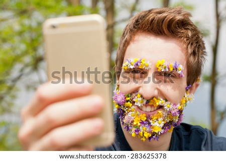 hipster man with flowers instead of his beard and eyebrows texting with his mobile phone - stock photo
