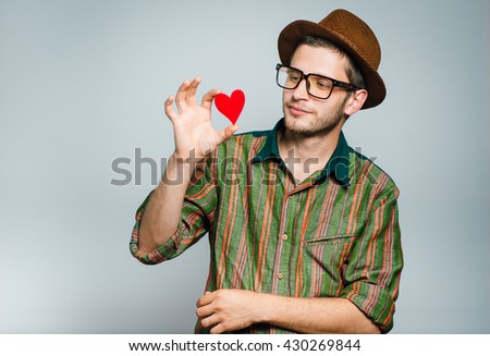 hipster man with heart - a symbol of love, wears glasses and hat, isolated on gray background - stock photo