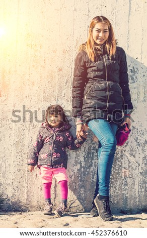 hipster mother and daughter 2 years post same point with wall be-hide so lovely family  ,vintage style tone - stock photo