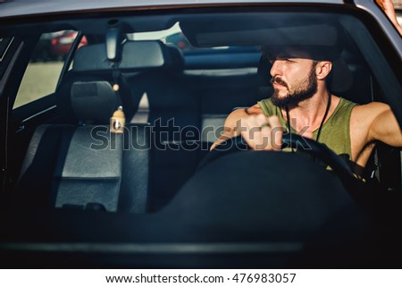 Hipster muscled man driving a car on a sunny day