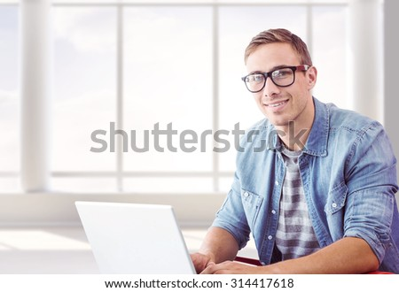 Hipster on laptop against room with large window - stock photo