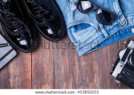 Hipster outfit on wooden background, top view