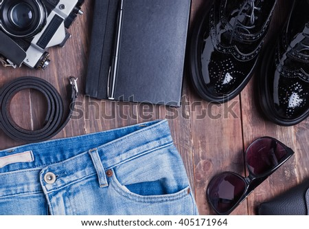 Hipster outfit on wooden table, top view