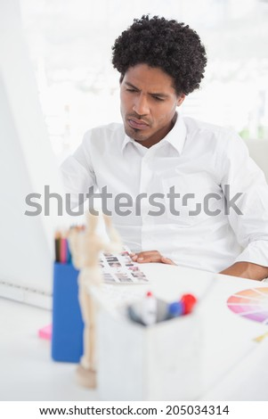Hipster photo editor working at his desk in his office - stock photo