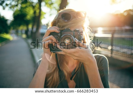 Hipster photographer using retro camera. Tourist girl capturing the moment
