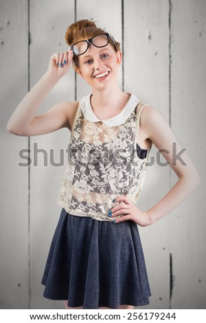 Hipster redhead smiling at camera against white wood - stock photo