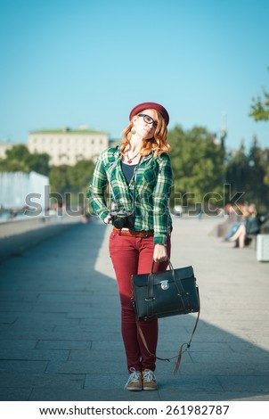 Hipster redhead woman in hat and glasses with retro camera outdoor