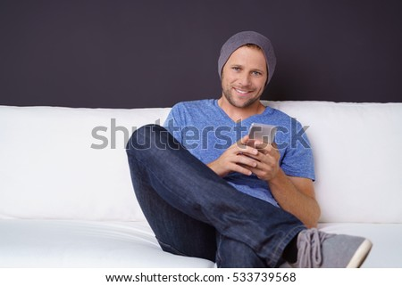 Hipster sitting on sofa texting a message looking at camera with a smile