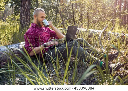 Hipster sitting on the ground with a laptop and drinking from a cup