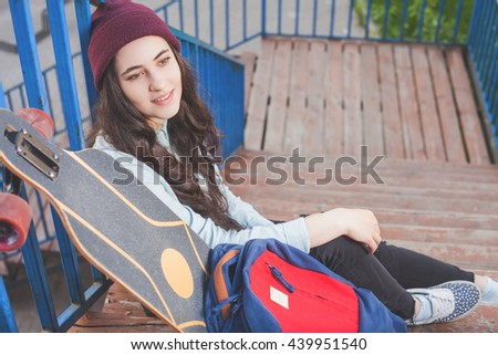 Hipster skateboarder girl with skateboard standing outdoor on stairs. Skatebord at city, street. Cool, Funny Tenager. Skateboarding at Summer