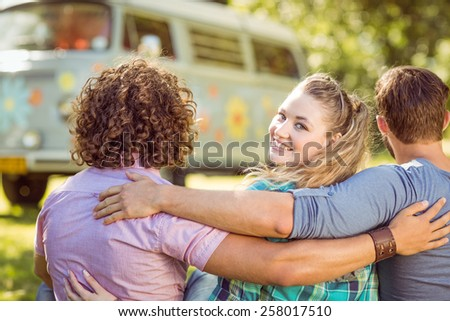 Hipster smiling at camera with friends on a summers day - stock photo