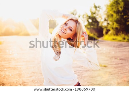 Hipster smiling girl standing outdoors on a sunny summer day. Vintage color - stock photo