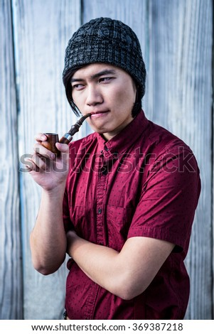 Hipster smoking pipe on wooden background