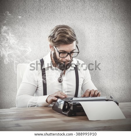 Hipster smoking pipe while working on typewriter against grey wall