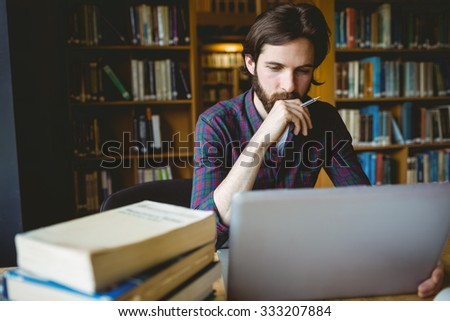 Hipster student studying in library at the university - stock photo
