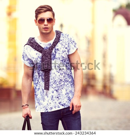 Hipster style guy. Fashion man standing near a wooden door  - stock photo