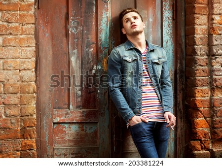 Hipster style guy. Fashion man standing near a wooden door and smoking - stock photo