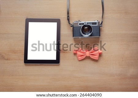 Hipster style. Overhead of objects on wooden background. Concept of the photographer. retro camera, digital tablet, bowtie. - stock photo